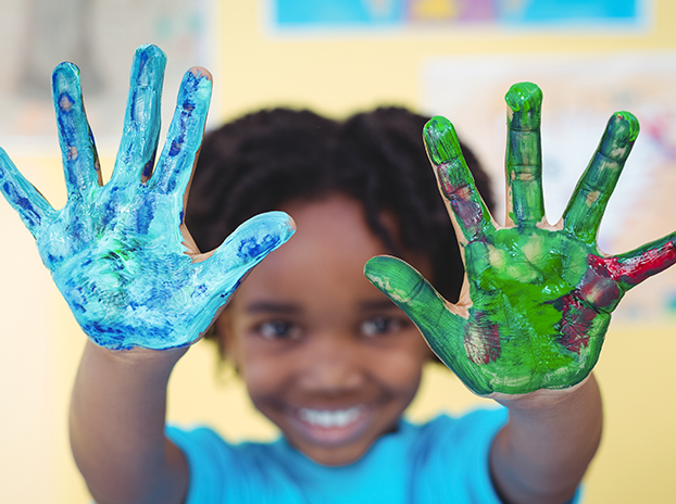 Child's hands covered with colorful paints
